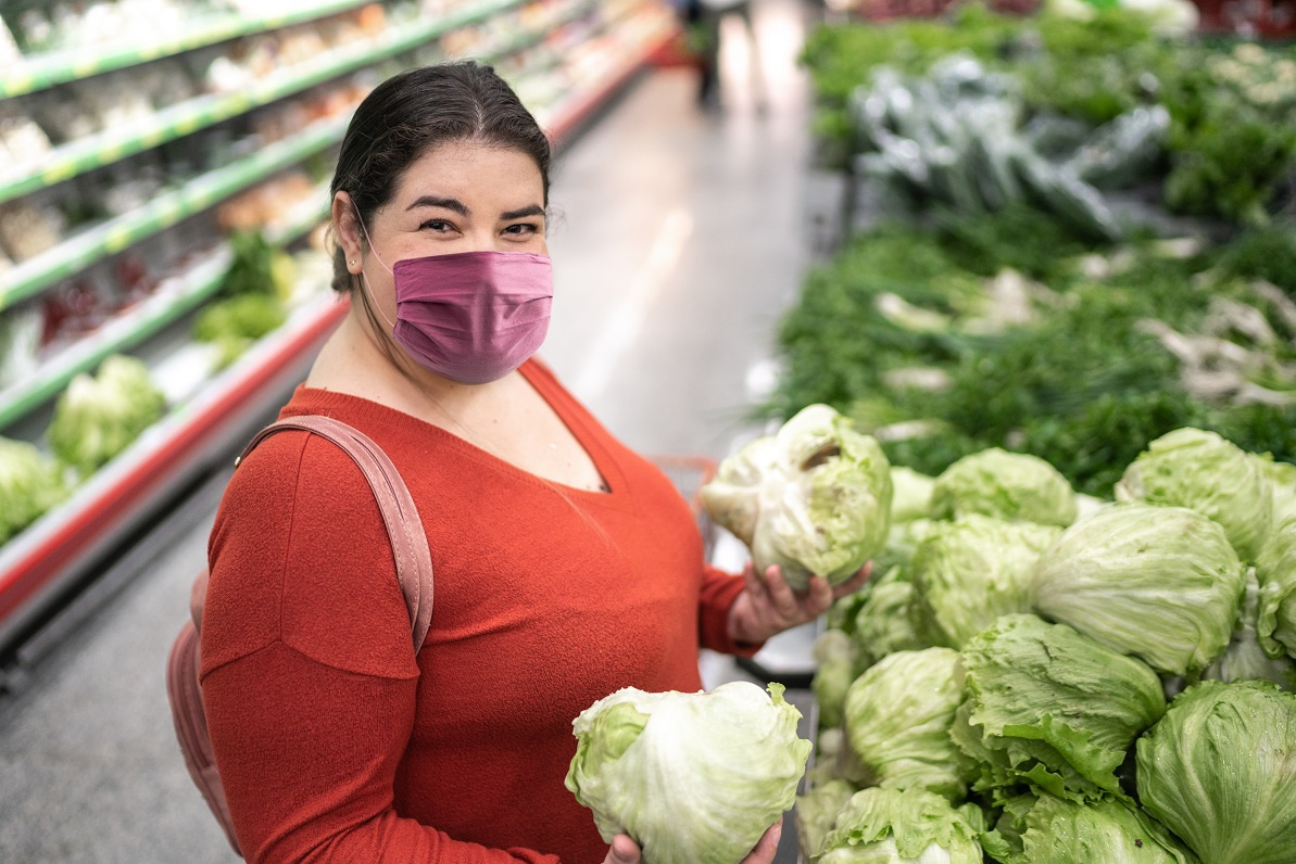 Woman holding groceries wearing mask