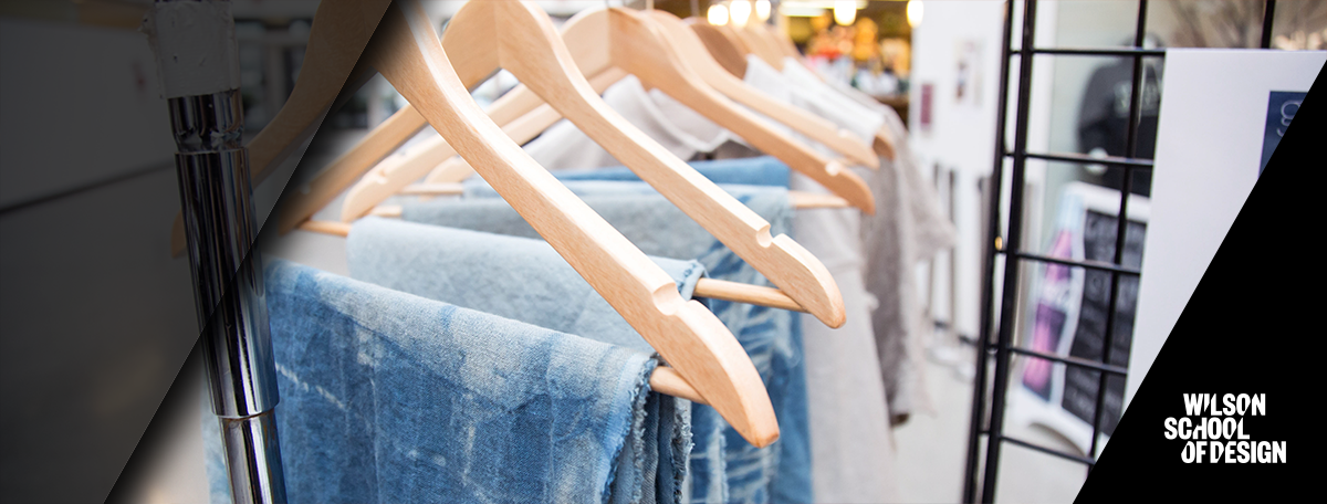 Row of jeans on hangers hanging up.