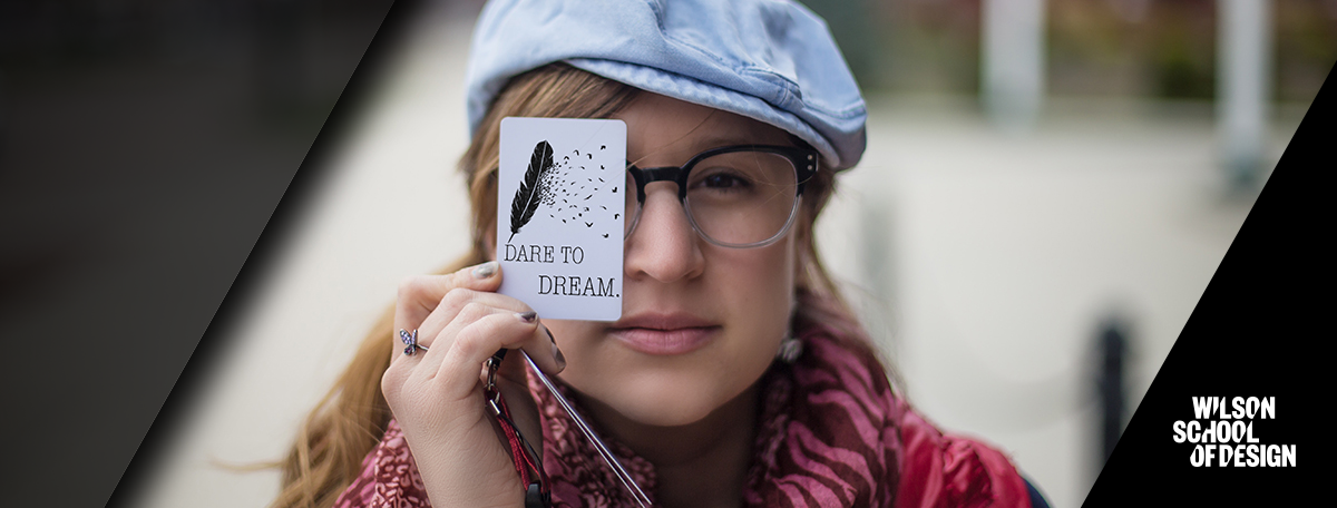 Design student with business card held up and covering one eye.