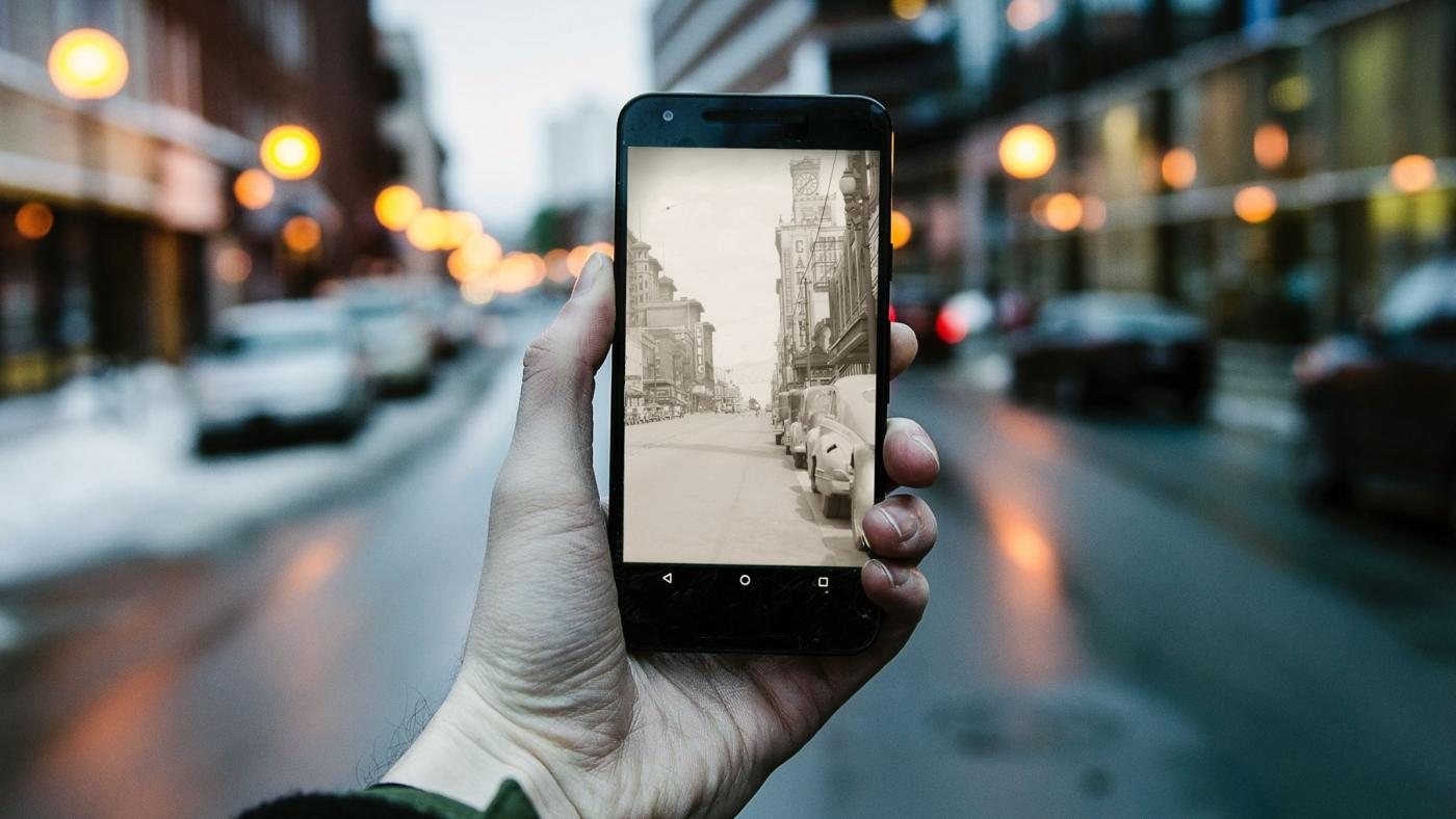 A photograph of a mobile phone captures the past and present appearance of a street