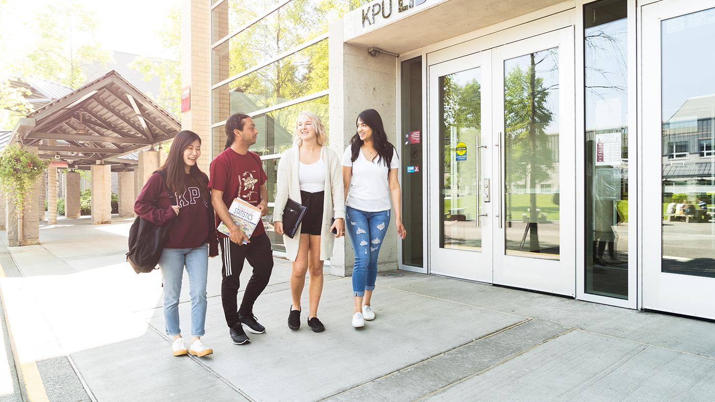 Image of four KPU students outside the KPU Surrey library. They are smiling as they walk and chat with each other.