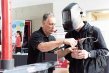 An instructor shows an attendee at a KPU open house how to use the virtual welding machine.